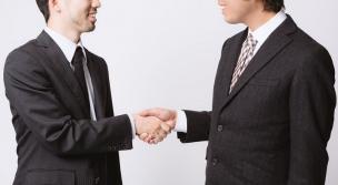取引が成立し握手を交わすスーツ姿の男性2人